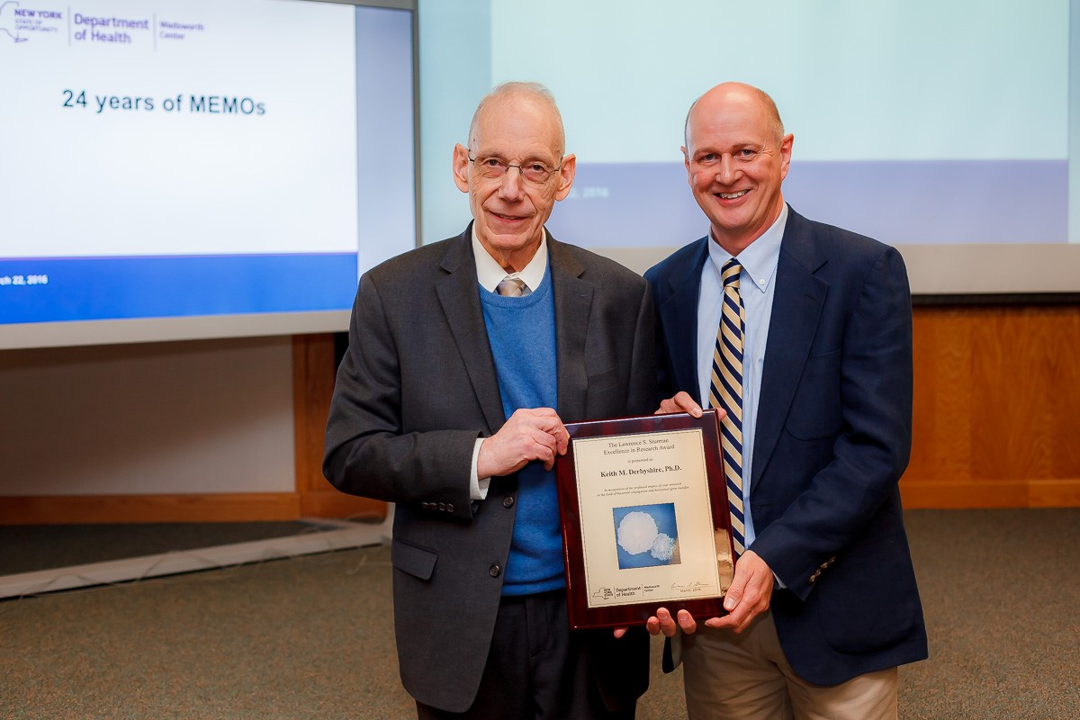Dr. Lawrence Sturman, left, presents the 2016 research award named in his honor to Dr. Keith Derbyshire.
